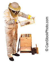 Honey and Comb - a beekeeper holding up a frame with honey...
