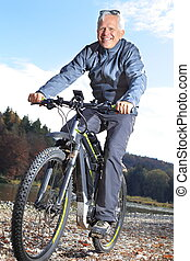 Senior on e-mountain bike beside a river - A Senior on...