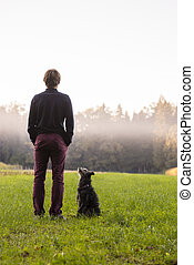 Young man standing in the middle of green meadow with his black dog sitting looking at him
