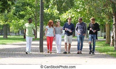 Group of stylish students with notebook on footpath outdoor...