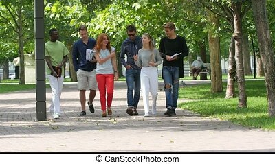 Group of happy students with notebook on footpath outdoor.