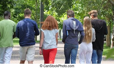 Group stylish student with notebook on footpath outdoor back...