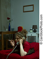 Lonely woman smoking cigarette and talking on the phone