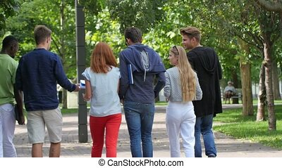 Group of students on footpath outdoor. back view - Group of...