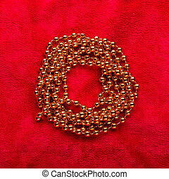 Christmas golden beads on red background.
