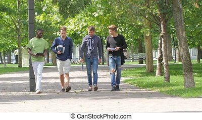 College students boy walking together on campus - Full...