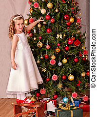 Child with gift box near Christmas tree. - Little girl with...