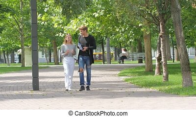 Couple of students in love walking along together on campus,...