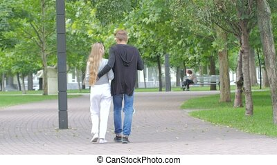Couple of students in love walking away together on...