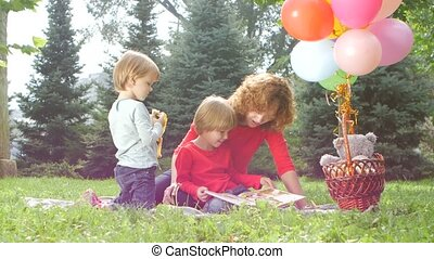 Happy mother with child daughter in park reading book