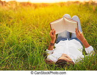 Young Woman Enjoying Book Reading Outdoors - Young Woman...