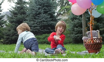 Two little girls with balloons in the park