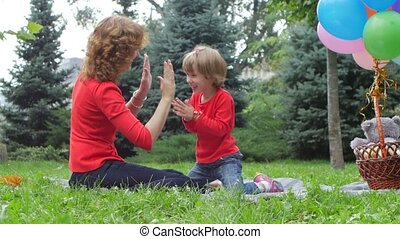 Clapping hands - mother playing with her daughter outdoor in...