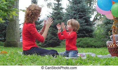 mother playing with her daughter outdoor in nature -...