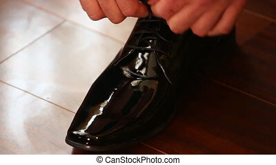 Man tying leather shoe - Close-up of tying the laces on...