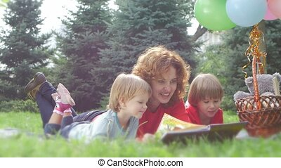 Happy Mom and  beautiful daughter reading a book in the park