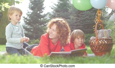 Mom and funny daughter reading a book together, in the park