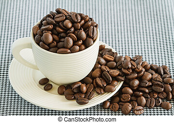 Coffee beans in white cup on table