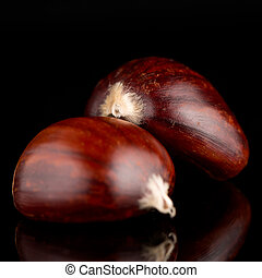 Chestnuts on a black reflective background - Closeup of...