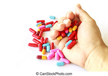 Various pills in hand on white background