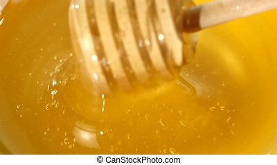 Using spoon for honey in bowl, pick it up, close up, macro -...