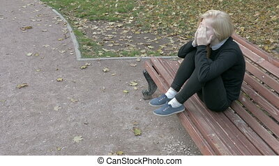Beautiful sad woman sitting in city park