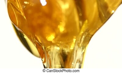 Thick honey dripping, on white - Thick honey dripping from...