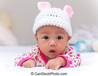 Portrait of cute newborn baby girl on the bed.