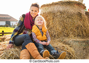 Portrait of happy woman with cute child sitting on hay on...