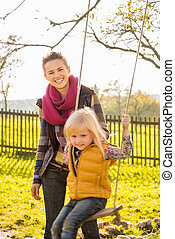 Portrait of smiling woman and swinging child in autumn...