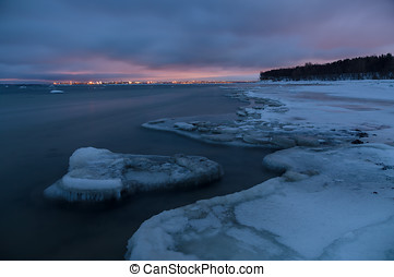Winter landscape of frosty seacoast and city lights by...