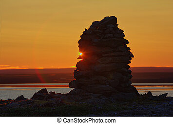 Built from stone Cairn at sunset, at midnight, the polar day...