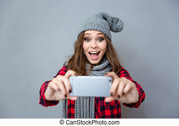 Cheerful woman doing photo on smartphone - Portrait of a...