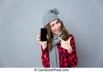 Woman winking and pointing finger on blank smartphone screen...