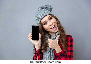 Woman showing blank smartphone screen and thumb up -...