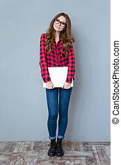 Smiling girl in glasses standing and holding laptop