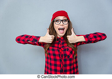 Cheerful hipster woman showing thumbs up - Portrait of a...