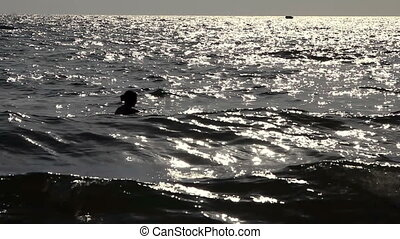 Silhouette of a girl swimming at the ocean
