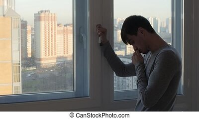 Worried man stand and crying near window - Worried man stand...