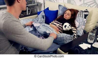 Husband covers a blanket sick wife in bed
