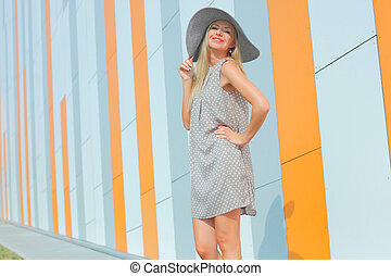 beautiful happy girl in a bright dress and a long hollow hat...