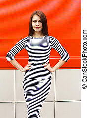 Beautiful woman wearing a striped dress in city over red