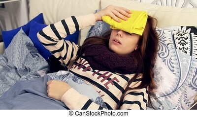 Sick woman with wet towel on forehead Compress - A sick...