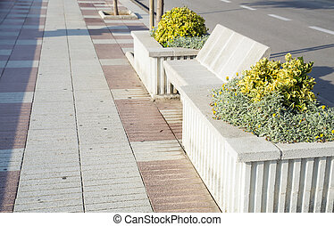 Street with stone benches and flower bed on the beach sunny...