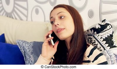 Depressed woman hearing bad news on phone at home -...