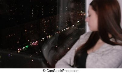 Sad woman sits on window sill, look at night city - Sad...