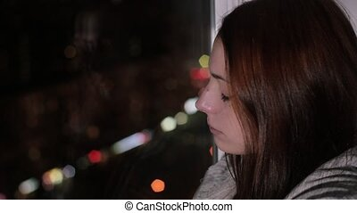 Sad redhead woman sits on window sill and crying - Sad...