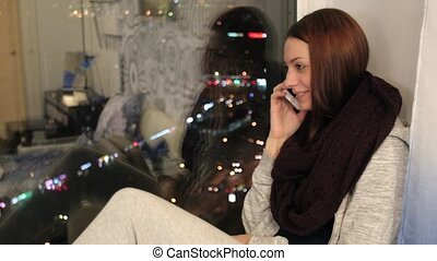 Girl sits on window sill and says goodbye on phone - Young...