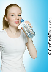 Young hot girl drinking water studio shot over blue...