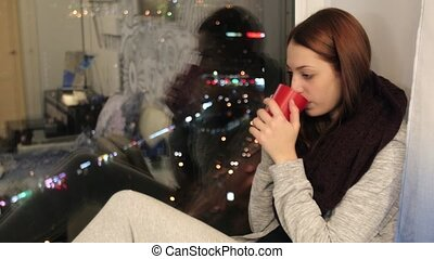 Girl sits on window sill and drinks hot tea in cup - Young...